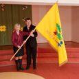 Kärla lasteaia direktor Maiu Raun ja lasteaia hoolekogu esindaja Koit Voojärv on rõõmsad, et Kärla lasteaia lipp on pärast kirikus toimunud õnnistamistseremooniat jõudnud oma kohale lasteaia saali.