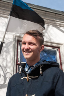 SINIMUSTVALGE ALL: Eilsel emakeelepäeval jäi Saaremaa juurtega Timothy L. Heinmets pildile Eesti lipu taustal. Foto: Raul Vinni