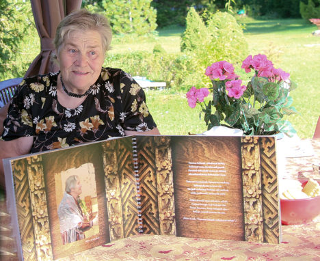 TÄNAVUNE JUUBILAR: 12. augustil 70-aastaseks saanud Tiiu Saan teisipäeval koduõues juubeliks kingitud albumiga, mis annab ülevaate tema isiknäitusest Kuressaare linnuses tänavuse aasta hakul. Foto: Irina Mägi