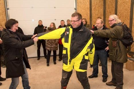 KAITSEÜLIKOND SELGA: Advokaat Maria Mägi-Rohtmets aitab saarevanemal Neeme Rannal ülikonda seljast võtta. Paremal ajakirjanik Indrek Rohtmets. Foto: Irina Mägi