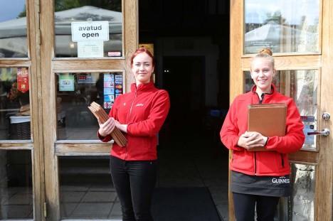 """TÖÖD ON PIISAVALT: Kuressaares asuva Vaekoja pubi teenindajad Kristin Reva (vasakul) ja Helina Kaal ütlevad, et suvel on tööd piisavalt ka kehvade ilmadega, kuid """"töö praegu konti ei murra"""". Kui augustis peaksid ilmad pikemalt ilusaks jääma, ei tähendaks see nende arvates kuigi palju rohkem kliente, sest põhiline turistide liikumise aeg on siiski juulikuu. Foto: Tõnu Veldre"""