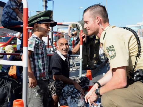 PRAEGU VEEL LAHKE: Pildil lubab heatahtlik Müncheni politseinik pagulaste lapsel oma vormimütsiproovida. Sotsioloogid hoiatavad aga, et kui rändekriisile lahendust ei leita, võib kvantiteet peagi kaasa tuua kvalitatiivse pöörde ja sakslaste meelsuses toimub järsk muutus. Esimesi tundemärke võib juba täheldada. Ibtimes.co.uk