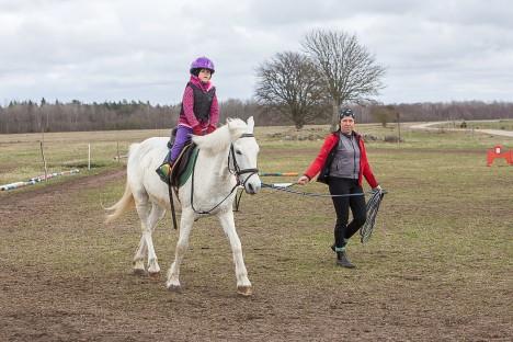 ÕPILANE JA TREENER: 7-aastane Loviise Mai tunneb ennast Aroomi seljas kindlalt. Treener Anne Udeküll Reinu ratsatalust julgustab ratsanikku, kinnitades hobuse korde külge. MAANUS MASING